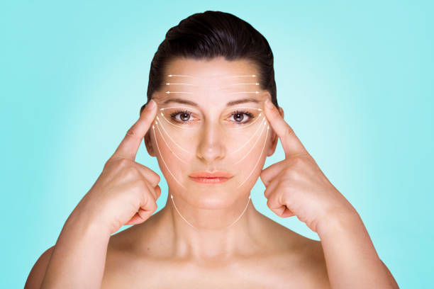 Face lifting Potrait of woman stretching her face skin against blue background. tighten stock pictures, royalty-free photos & images