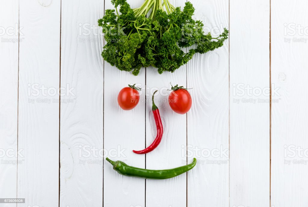 face made on different fresh seasonal vegetables on white wooden table background foto de stock royalty-free