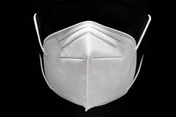 kn95 face mask isolated on black background - ffp2 imagens e fotografias de stock