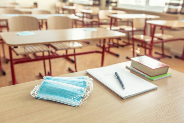 Face mask on a teachers and school desk in a school classroom. stock photo
