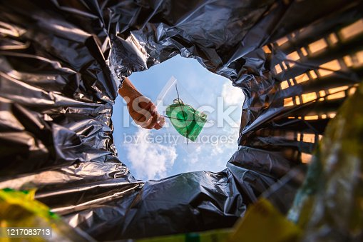 Face mask pack in zip lock before throw into the trash. With a worm view from the inside of the trash bin.