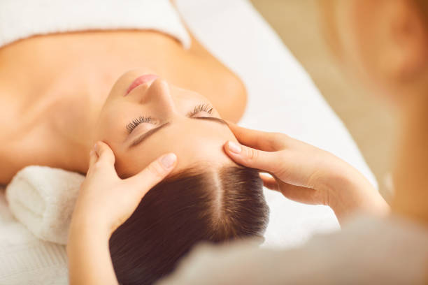Face massage close up. Beautiful girl has a facial massage. stock photo