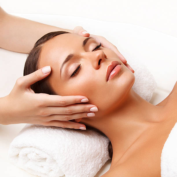 face massage.  close-up of a young woman getting spa treatment. - beauty treatment stock photos and pictures