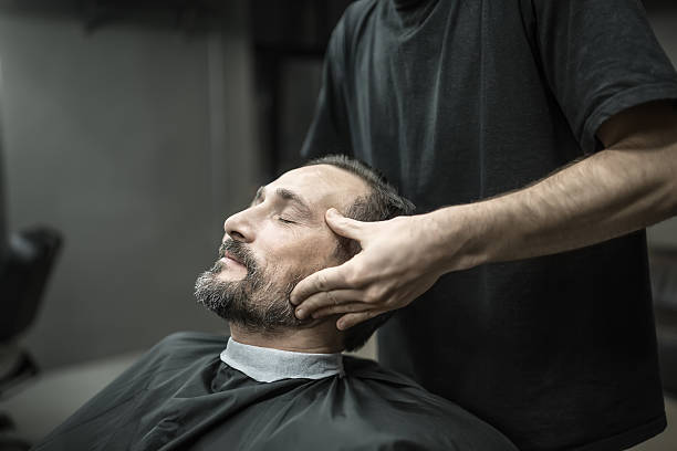Face massage in barbershop stock photo