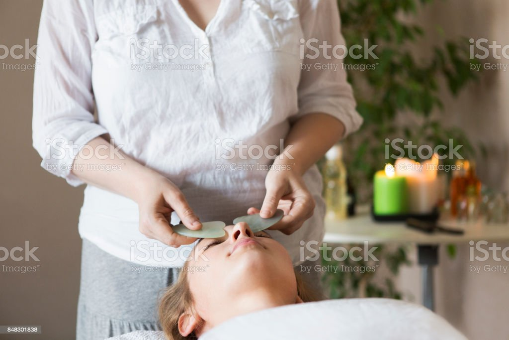 Face massage or beauty treatment in spa salon stock photo