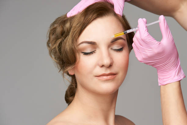 Face needle injection. Young woman cosmetology procedure. Doctor gloves. Brow between Face needle injection. Young woman cosmetology procedure. Doctor gloves. Brow between. between stock pictures, royalty-free photos & images