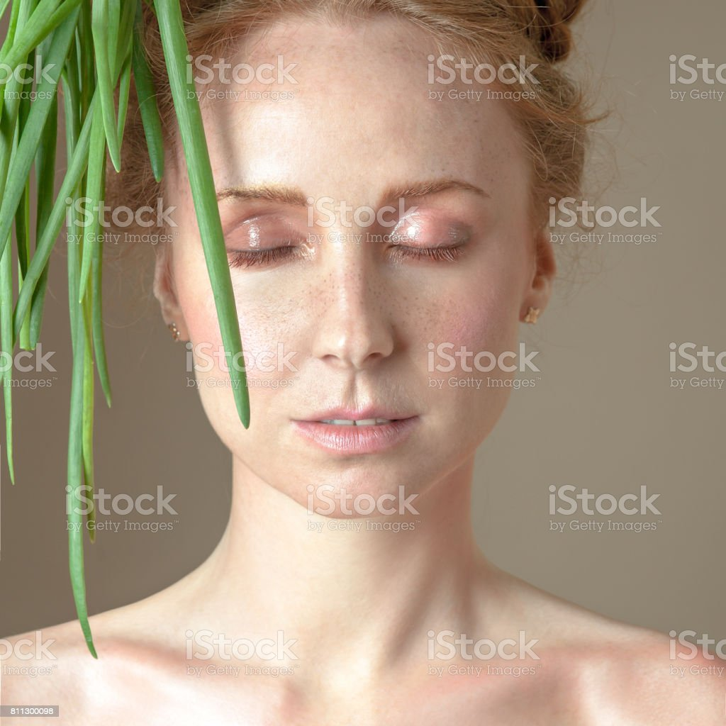 Face of a beautiful girl with shining gorgeous skin and dangling green onions stock photo