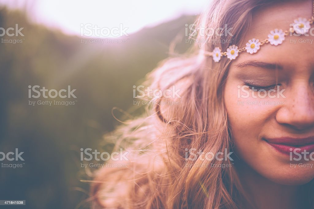 Face of a boho girl with a vintage flowered headband stock photo