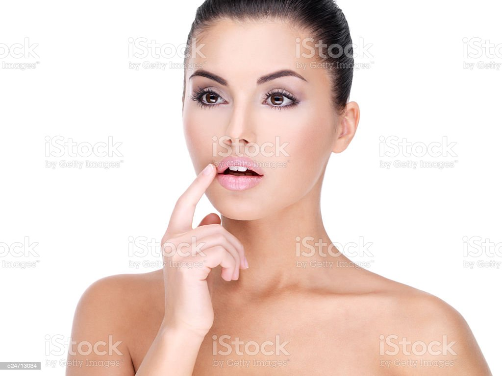 Face of a Pretty young woman with finger at  lips stock photo