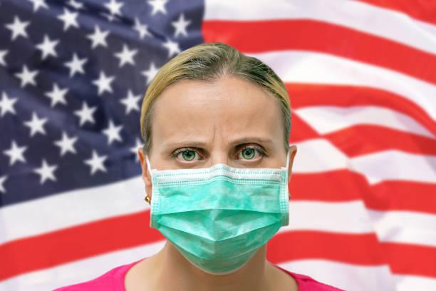 Gesicht einer Frau in einer Maske, die vor dem Hintergrund der US-Flagge in die Kamera schaut. Influenza aus Coronavirus, Prävention von Pandemie-Virus-Infektion. Virus in den USA. – Foto