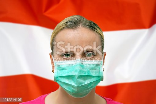 istock Face of a woman in a mask looking at the camera against the background of the Austria flag. Influenza from coronavirus, prevention of pandemic virus infection. Virus in Austria. 1212214107