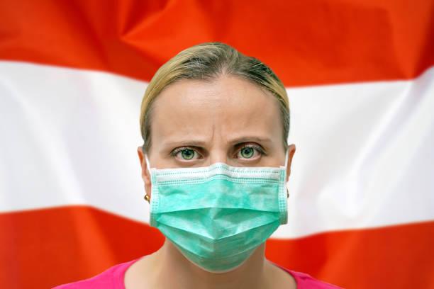 Gesicht einer Frau in einer Maske, die vor dem Hintergrund der Österreich-Flagge in die Kamera schaut. Influenza aus Coronavirus, Prävention von Pandemie-Virus-Infektion. Virus in Österreich. – Foto