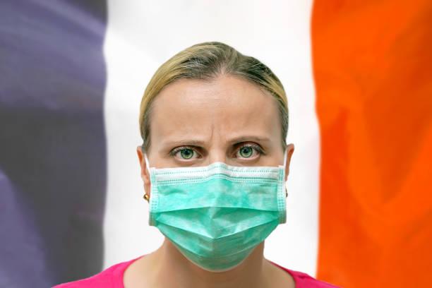Gesicht einer Frau in einer Maske, die vor dem Hintergrund der Frankreich-Flagge in die Kamera schaut. Influenza aus Coronavirus, Prävention von Pandemie-Virus-Infektion. Virus in Frankreich. – Foto