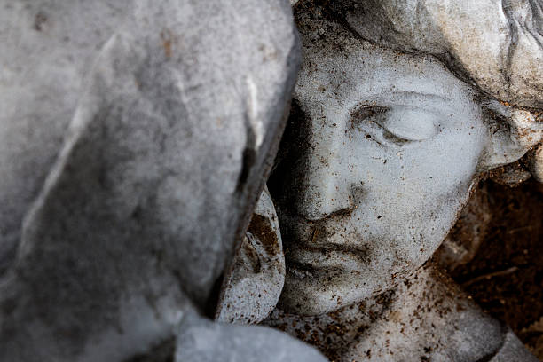 Face of a woman statue behind a rock stock photo