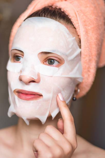 Face de uma mulher nova com um tecido que hidrata a máscara cosmética-procedimentos cosméticos - foto de acervo