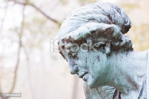 Closeup face of Angel, statue from cemetery build in 1850, Czech Republic, side view, background with copy space, horizontal composition