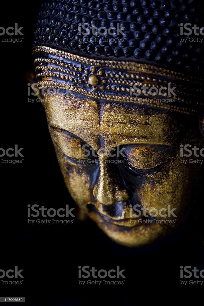 Face of Buddha statue in gold and blue on black background stock photo