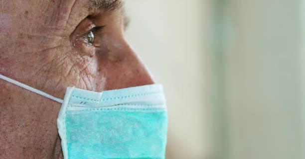face of elderly man wearing medical facemask - old men window imagens e fotografias de stock