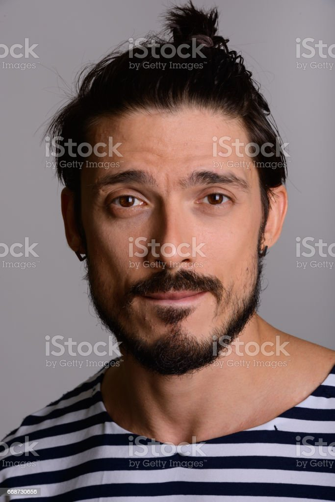 Face of handsome man hair tied back and biting lip stock photo