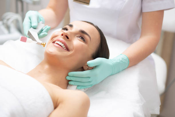 Face of happy lady and dermatologist holding metal tool stock photo