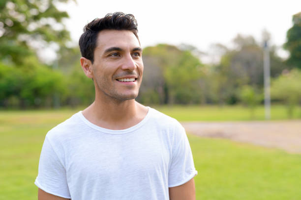 Face of happy young handsome Hispanic man thinking at the park stock photo