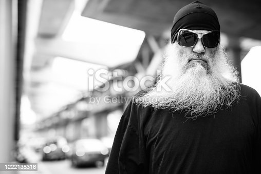 Portrait of mature handsome bearded hipster man with beanie hat in the city streets outdoors in black and white