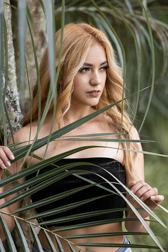 face of woman with long blonde hair with long leaves of a tree behind, beauty and lifestyle