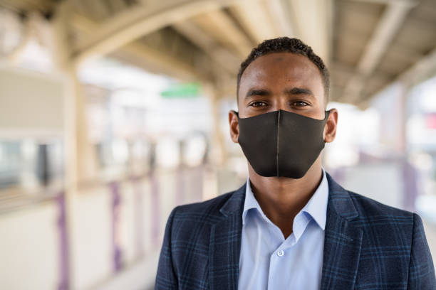 Face of young African businessman in suit with mask for protection from corona virus outbreak at the sky train station stock photo