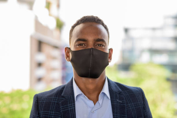 Face of young African businessman wearing mask for protection from corona virus outbreak against view of the city stock photo
