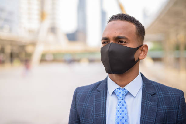 Face of young African businessman with mask for protection from corona virus outbreak thinking in the city stock photo