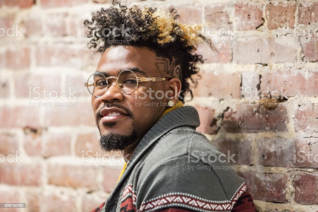 Face of young mixed race man leaning on brick wall stock photo
