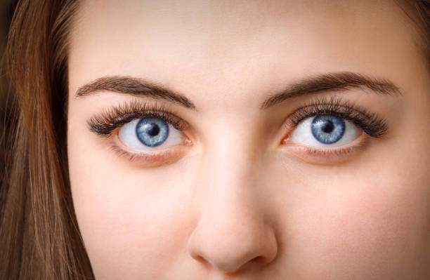 face of young woman with long eyelashes stock photo