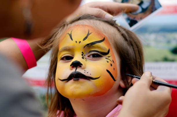 Face painting Cute little girl with face painted like a lion. carnival children stock pictures, royalty-free photos & images