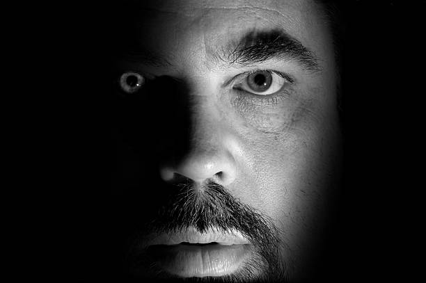 Face Close-up portrait. An exercise in light and shadow. creepy stalker stock pictures, royalty-free photos & images