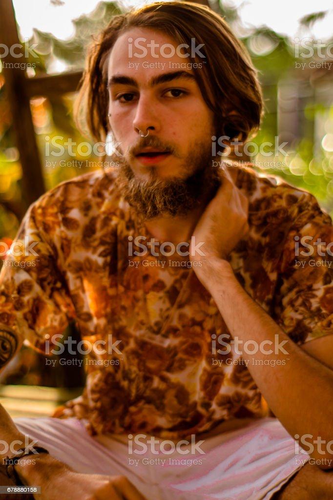 Face portrait d'un jeune homme avec barbe et cheveux bruns, nez oreille piercing et exotique photographié au crépuscule photo libre de droits