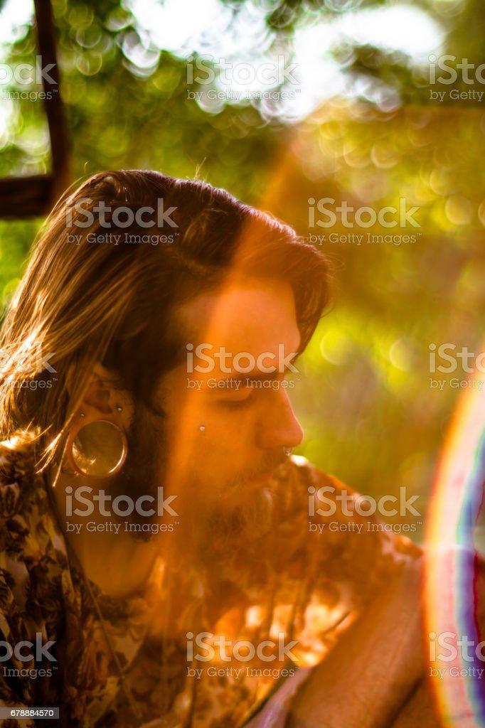Sakal ve kahverengi saç, burun piercing ve egzotik küpe gece karanlığında fotoğraflandı olan genç bir adam portresi yüz royalty-free stock photo