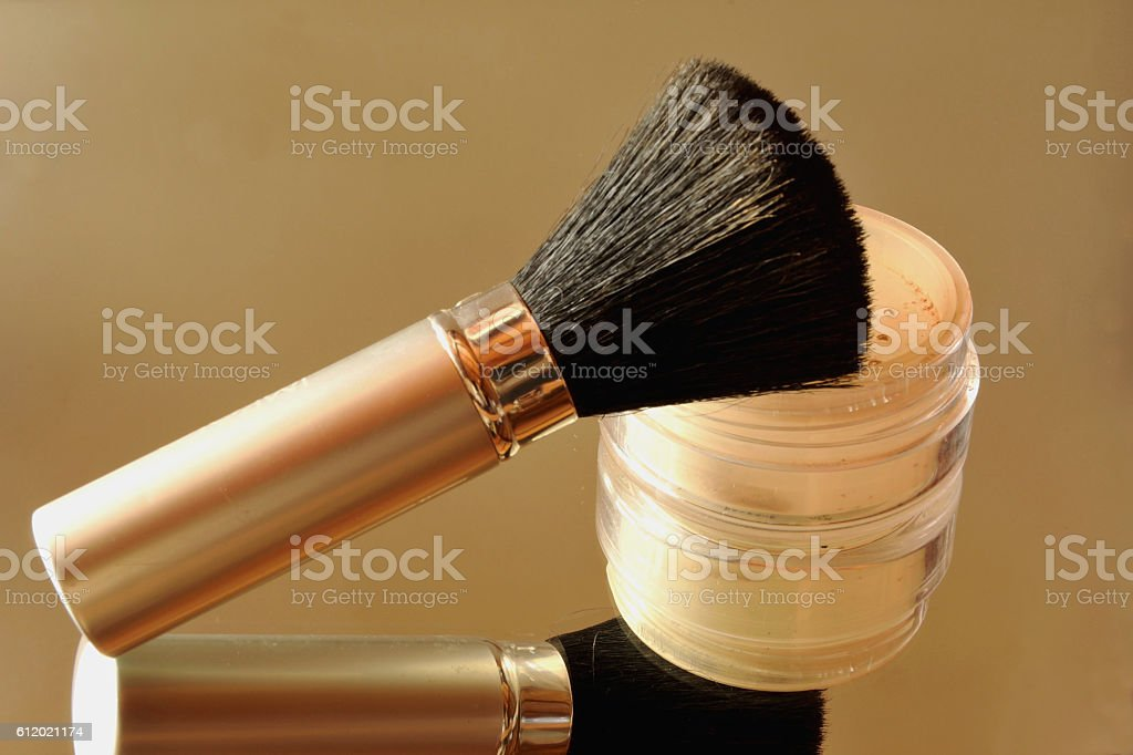 Face powder a brush and their reflection in the mirror stock photo