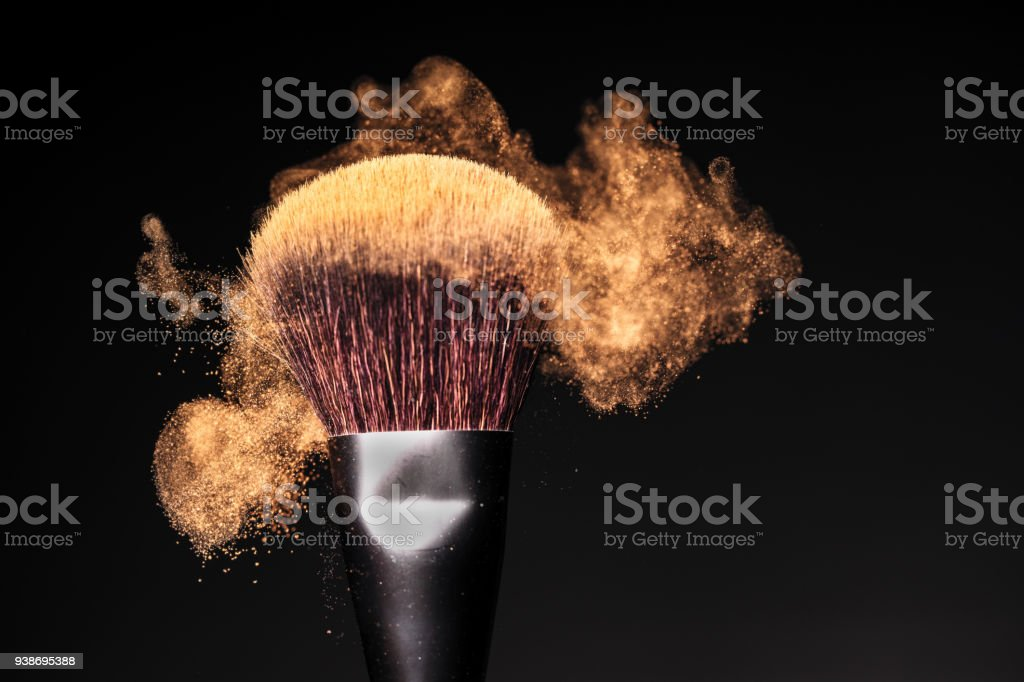 Face powder in motion on a make-up brush on a black studio background stock photo