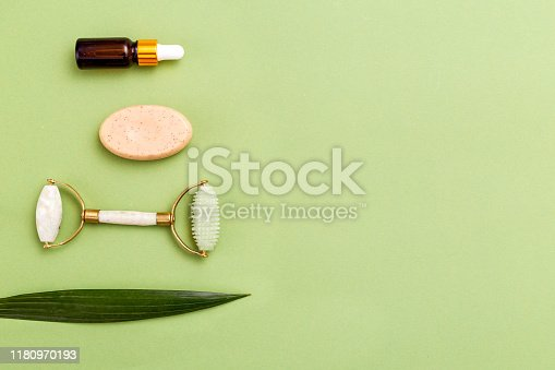 Face roller and beauty product on green background. Copy space. Minimal