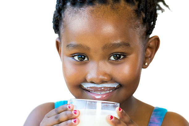 Face shot of sweet african girl with milk mustache. stock photo
