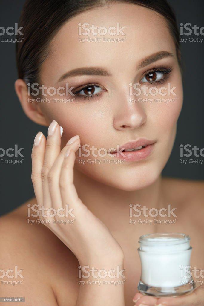 Haut-Gesichtspflege. Schöne Mädchen, die weiche, glatte Haut Creme aufsetzen - Lizenzfrei Attraktive Frau Stock-Foto