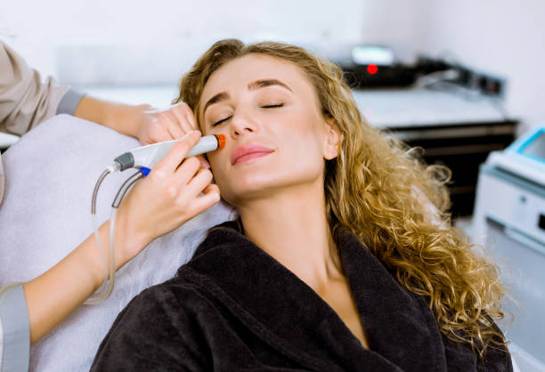 Face Skin Care. Close-up of pretty blond curly woman getting facial hydro microdermabrasion peeling treatment at cosmetology Spa Clinic. Hydra Vacuum Cleaner. Exfoliation, Rejuvenation, Hydratation. Face Skin Care. Close-up of pretty blond curly woman getting facial hydro microdermabrasion peeling treatment at cosmetology Spa Clinic. Hydra Vacuum Cleaner. Exfoliation, Rejuvenation, Hydratation rymdraket stock pictures, royalty-free photos & images