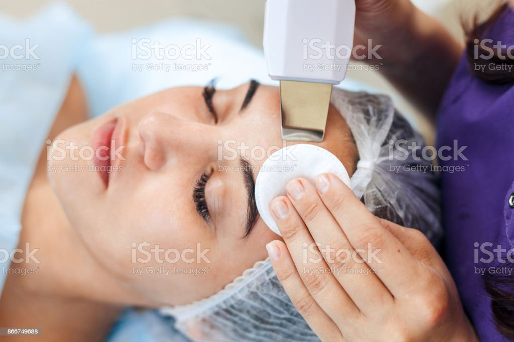 Face skin care. Woman getting facial ultrasound cleaning stock photo