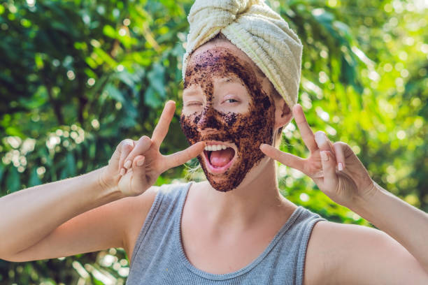 face skin scrub. portrait of sexy smiling female model applying natural coffee mask, face scrub on facial skin. closeup of beautiful happy woman with face covered with beauty product. high resolution - muso foto e immagini stock
