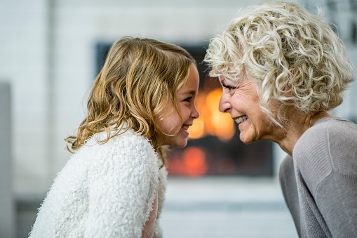 A Caucasian grandmother and granddaughter are indoors in their living room. They are sitting together and lovingly looking at each other. There is a fireplace in the background.