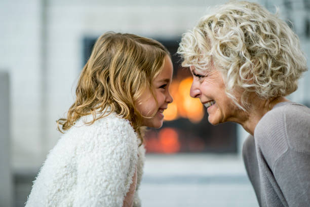 Face To Face A Caucasian grandmother and granddaughter are indoors in their living room. They are sitting together and lovingly looking at each other. There is a fireplace in the background. face to face stock pictures, royalty-free photos & images