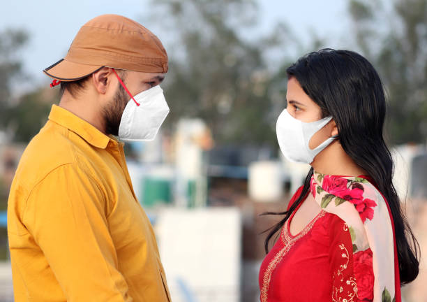 Face to face Portrait of young Indian couple standing outdoors with covering face mask against COVID-19 stock photo