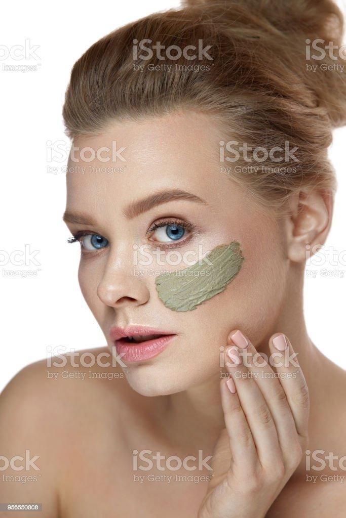 Gesichtsbehandlung. Schöne Frau mit Streifen von Tonerdemaske - Lizenzfrei Attraktive Frau Stock-Foto