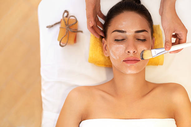 face treatment. woman in beauty salon gets marine mask - beauty treatment stock photos and pictures