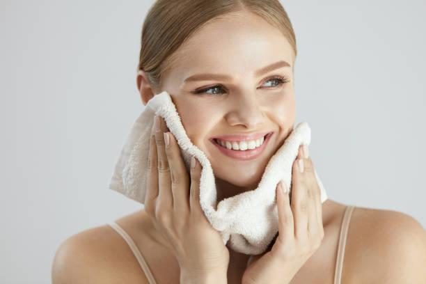 顔洗う。タオルで肌を乾燥幸せな女 ストックフォト